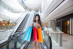 Beautiful young woman shopping in mall. Holding shopping bags standing on escalator Stock Photo