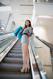 Beautiful young woman shopping in mall. Holding shopping bags standing on escalator Royalty Free Stock Images