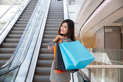 Beautiful young woman shopping in mall. Holding shopping bags standing on escalator Stock Images