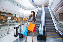 Beautiful young woman shopping in mall. Holding shopping bags standing on escalator Stock Photos