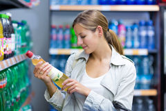 Beautiful young woman shopping in a supermarket Stock Images