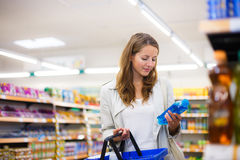 Beautiful young woman shopping in a supermarket Royalty Free Stock Images