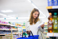 Beautiful young woman shopping in a supermarket Royalty Free Stock Photos