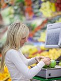 Beautiful young woman shopping for vegetables Royalty Free Stock Photo