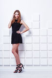 Beautiful young woman in short black dress and black shoes. Full-length portrait of beautiful young woman in short black dress and black shoes Royalty Free Stock Photo