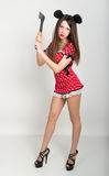 Beautiful young woman in a short dress with polka dots, in her hand holding the ax Royalty Free Stock Photo