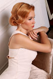 Beautiful young woman with short red hair in retro style,wears elegant white dress Stock Photography