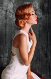 Beautiful young woman with short red hair in retro style,wears elegant white dress Stock Photos