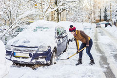 Beautiful young woman shoveling her car Stock Images
