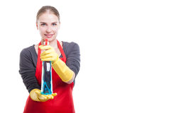 Beautiful young woman showing cleaning spray at camera. And smiling on white background with text space Stock Image