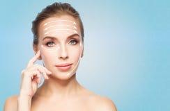 Beautiful young woman showing her cheekbone Stock Photos