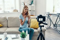 Beautiful young woman. Showing her hair tips while making social media video at home royalty free stock image