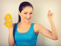 Beautiful young woman showing her strong bicep muscle and holdin. G slices of fresh fruit orange with happy smiling. Toned closeup portrait Stock Photo