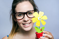Beautiful young woman showing one artificial daisy Stock Images