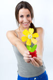 Beautiful young woman showing one artificial daisy Royalty Free Stock Photos