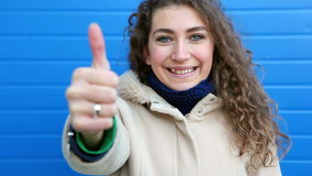 Beautiful young woman showing thumb up and smile, leaning against blue wall stock video