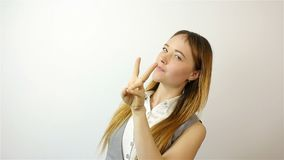 Beautiful young woman showing victory sign and smiling. On white Background stock footage