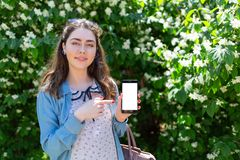 A beautiful young woman shows her index finger on a mobile phone. Green plants on a background. Copy space and mock up. Concept of. Modern technology and royalty free stock photography