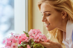 Beautiful young woman. Side view of a beautiful young woman enjoying the scent of flowers, close-up royalty free stock image