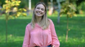 Beautiful young woman sincerely smiling on camera in park, rest and wellness stock footage