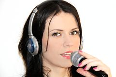 Beautiful young woman singing and listening to music with headphones Stock Images