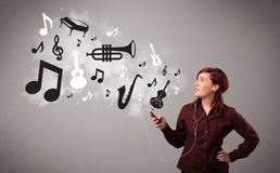 Beautiful young woman singing and listening to music with musica Stock Images