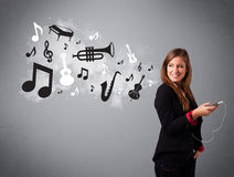 Beautiful young woman singing and listening to music with musica. L notes and instruments getting out of her mouth Royalty Free Stock Photo
