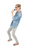 Beautiful young woman singing into a microphone Royalty Free Stock Images