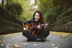 Beautiful young woman singing and playing guitar. Stock Photography