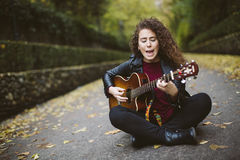 Beautiful young woman singing and playing guitar. Stock Image
