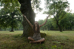 Beautiful young woman sit under a tree stock photo