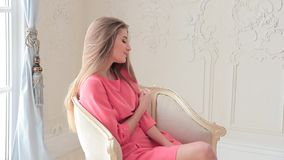 Beautiful young woman siting on chair in pink dress and posing to photographer stock video