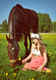 Beautiful young woman sits in the field with a horse Royalty Free Stock Images