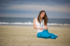 Beautiful young woman sits on sand near the ocean Stock Image