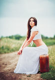 Beautiful young woman sits on suitcase near field road Stock Photos