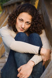 Beautiful young woman is sitting. Young beautiful woman with arms crossed Royalty Free Stock Photo