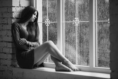 Beautiful young woman sitting alone close to window with rain drops. Sexy and sad girl. Concept of loneliness. Black Stock Photo