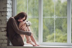 Beautiful young woman sitting alone close to window with rain drops. Sexy and sad girl. Concept of loneliness Royalty Free Stock Images