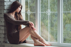 Beautiful young woman sitting alone near window with rain drops. Sexy and sad girl. Concept of loneliness Royalty Free Stock Photos