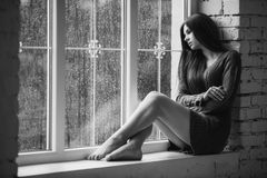 Beautiful young woman sitting alone near window with rain drops. Sexy and sad girl with long slim legs. Concept of Royalty Free Stock Image