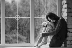 Beautiful young woman sitting alone near window with rain drops. Sexy and sad girl with long slim legs. Concept of. Loneliness. Black and white Royalty Free Stock Photo