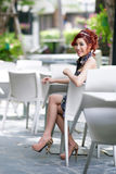 Beautiful young woman sitting alone in street cafe Stock Photography