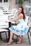 Beautiful young woman sitting alone in street cafe Stock Images