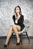 Beautiful young woman sitting in a armchair. Black dress, shoes and stockings Royalty Free Stock Image