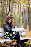 Beautiful young woman sitting in the autumn park with her dog Royalty Free Stock Photos