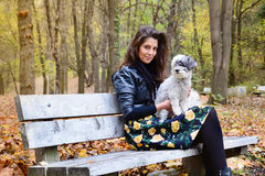 Beautiful young woman sitting in the autumn park with her dog Royalty Free Stock Images
