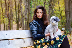 Beautiful young woman sitting in the autumn park with her dog Royalty Free Stock Photography