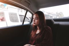 Beautiful young woman is sitting on back seat in the car. 