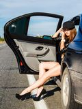 Beautiful young woman sitting at the back seat of a car Royalty Free Stock Photography