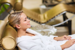 Beautiful young woman sitting in bath robe at spa Stock Images